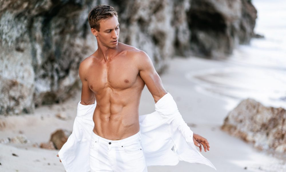 Sexy muscular man in a white shirt with a bare-chested resting on the beach, ocean waves at background. Tanned guy posing on vacation